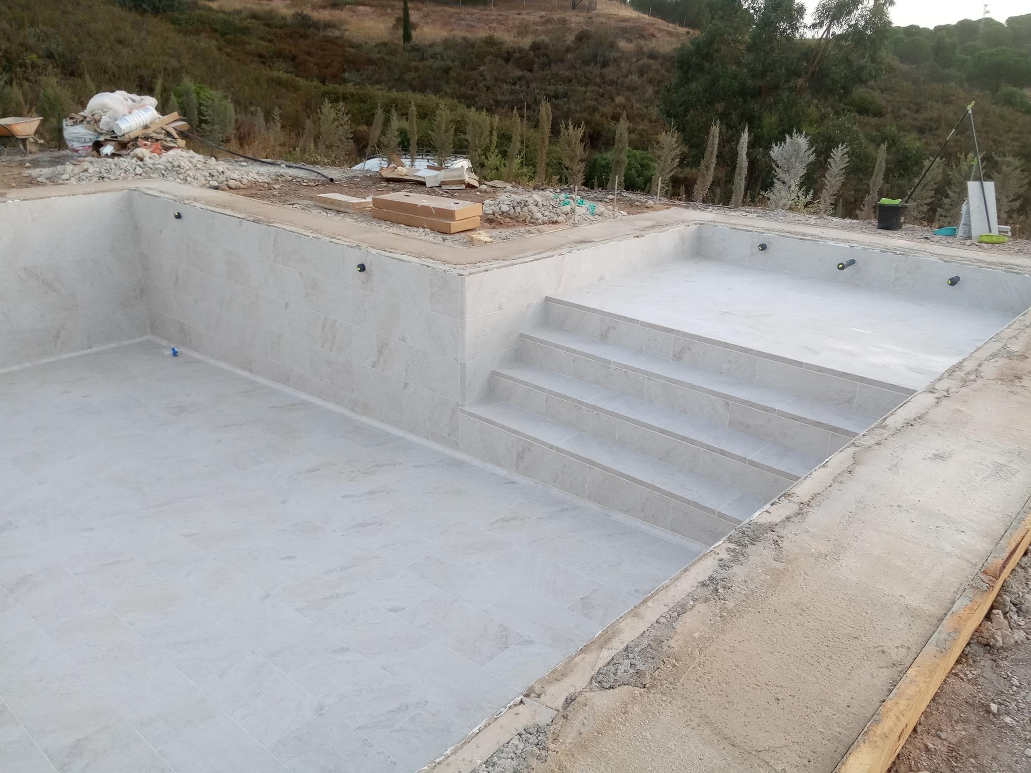 instalación del gres en la piscina en obras.