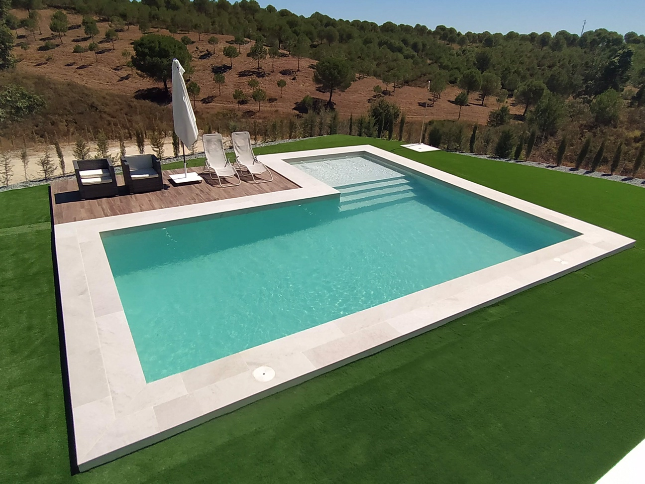 Vista frontal de la piscina revestida con porcelánico White Stone, situada en entorno natura.